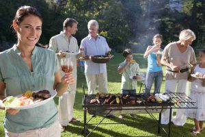Three generation family standing beside barbecue grill in garden, focus on woman holding plate of food and glass of wine in foreground, smiling, portrait